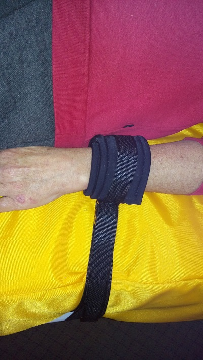 Arm Immobiliser attached to bed and patients wrist